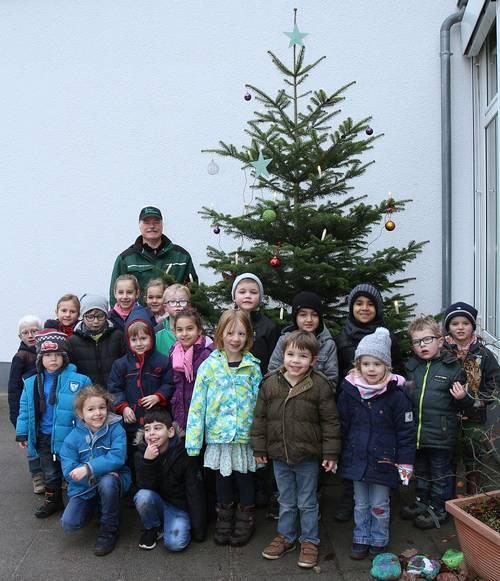 Kinder freuen sich über Tannenbaum
