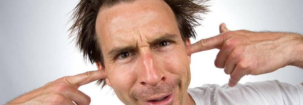 Mann steckt Finger in die Ohren gegen Lärm